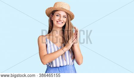 Young beautiful blonde woman wearing summer hat clapping and applauding happy and joyful, smiling proud hands together