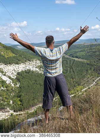 An Adult Man With His Arms Spread Wide, Seen From The Back, Stands On The Edge Of A Precipice.