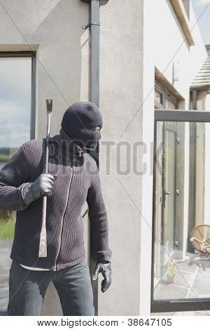 Robber hiding behind a wall with crow bar