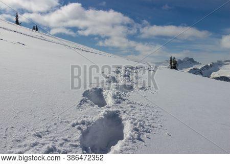 Feet Imprints In Fluffy Deep Snowdrift On The Hillside. Concept Background Active Winter Holidays. H