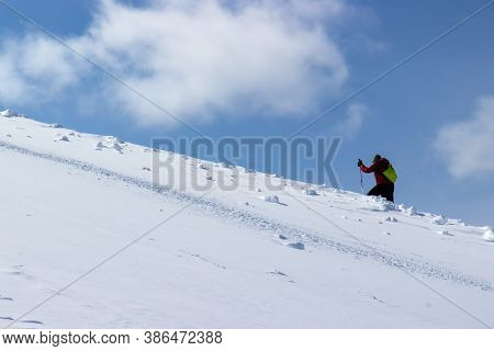 One Unrecognizable Person Climb Skiing On A Snowy Hillside In Sunny Winter Day. Skier Hiking To Summ