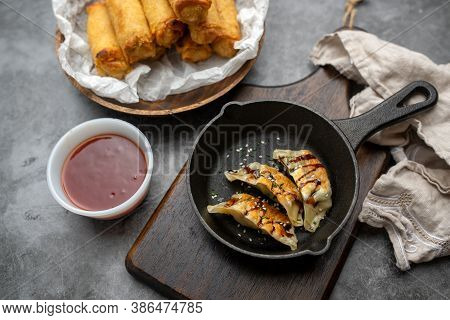 Fried Potstickers With Balsamic Glaze Covered In Seeds And Chives