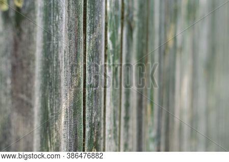 Old Wooden Planks With Peeling Green Paint. The Texture Of A Weathered Wooden Fence. Abstract Multit