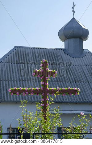 Wooden Crucifix Decorated With Flowers On The Background Of A Christian Church. Religious Holiday In