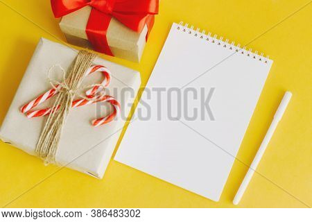 Christmas Composition With Notepad For Your Text. Notepad, Pen, Gift Boxes, Christmas Striped Candy