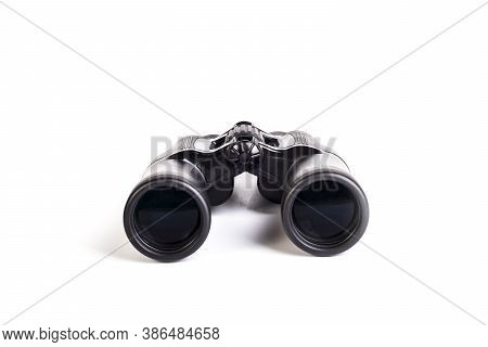 Modern Binoculars In Black On A White Background. Lenses Forward. Close-up. There Is No Isolation