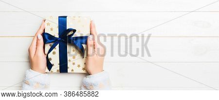 Woman Hands Give Wrapped Christmas Or Other Holiday Handmade Present In Colored Paper . Present Box,