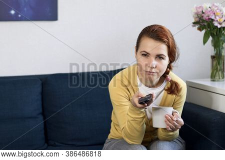 Bored Lonely Young Woman Sitting On Sofa In Living Room, Watching Tv, Switching Channels With Tv Rem