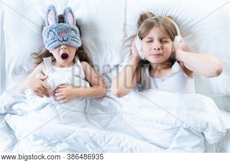 Little Girls Sleep In Bed. One Is Snoring Hard,sister Is Covering Ears With Fur Headphones.early Mor