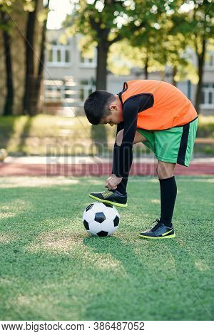 Close Up Young Football Player Which Puts His Leg On Ball And Tying Shoelace On Soccer Stadium Durin