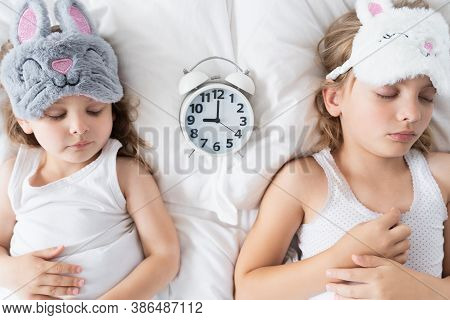 Little Girl, Sisters Sleep In Bed With Big Alarm, Clock. Soft Cat, Bunny Mask. Early Morning Rise To