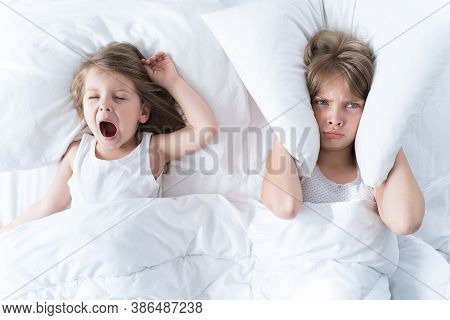 Little Girls Sleep In Bed. One Is Snoring Hard, Sister Is Covering Her Ears With Pillow. Early Morni