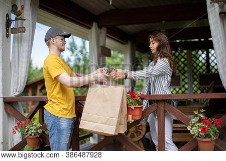 Delivery Man Handing Paper Bags To Female Recipient, Beautiful Young Woman Customer Receiving Order