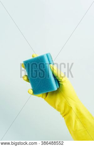 Yellow Rubber Glove Is Holding Sponge On The Blue Background. Yellow Rubber Glove Is Cleaning With S
