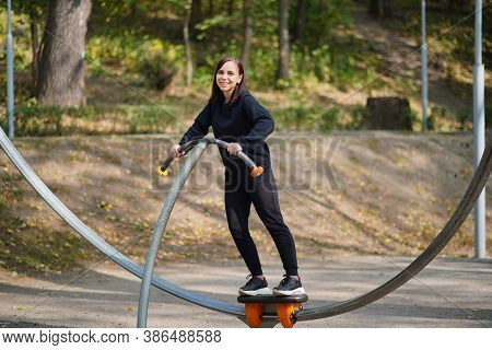 Young Woman In Casual Clothes Doing Sports In Park. Adult Female Doing Sports Exercises On Street Si