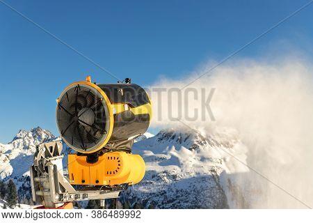 Operating Artificial Snow Cannon Near Piste Making Snowy Powder.ski Lift Ropeway On Hilghland Alpine