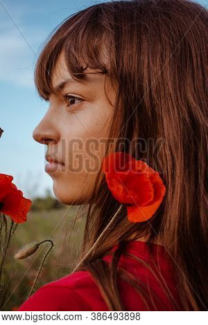 A Young White Teen Girl Portrait Close-up In Profileon Nature Meadow With Red Blooming Poppies Flowe