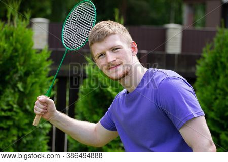 Portrait Of Male Badminton Player Holds Racket In Hands. Young Fit Athletic Man Playing Badminton Ou