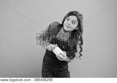 Girl Going To Take Pill Or Vitamin. Little Girl Opening Cream Plastic Bottle. Products For Children.