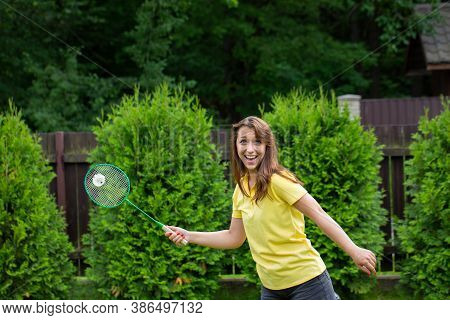 Young Enthusiastic Woman Playing Badminton Outdoors. Female Badminton Player With Racket In Action.