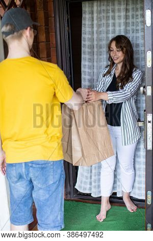 Beautiful Woman Customer Receiving Order From Courier At Home, Delivery Man In Yellow Uniform Handin
