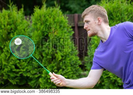 Young Concentrated Handsome Man Playing Badminton Outdoors In Park. Badminton Player With Racket In