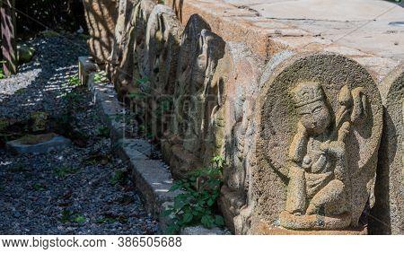 Geumsan, South Korea; September 12, 2020: Rock Carved Monks On Brick Base Of Structure At Dongguksa