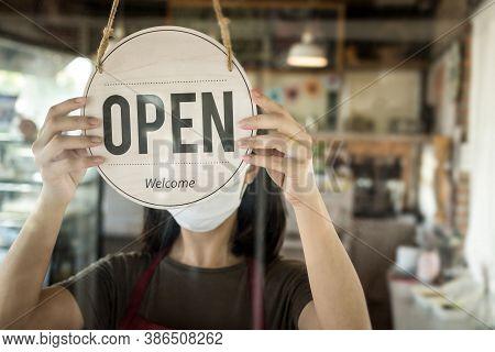 Restart. Waitress Woman Turning Open Sign Board Reopen After Coronavirus Quarantine Is Over In Moder