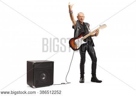 Full length portrait of a rocker with a guitar plugged into an amplifier gesturing a rck and roll sign isolated on white background