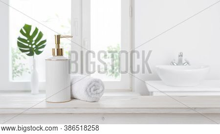 Soap Dispenser On Table Against Blurred Bathroom Window Background