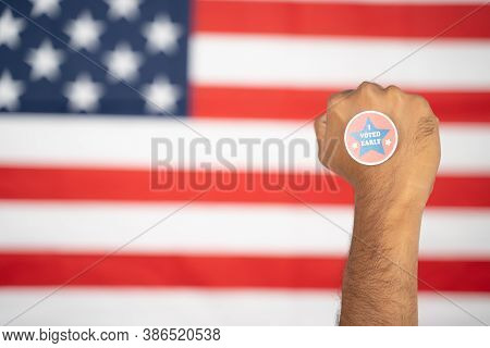 Rising Fist With I Voted Early Sticker On Hand With Us Flag As Background - Concept Of Early Voting