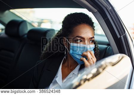 Young Businesswoman Being A Taxi Passenger And Having A Ride Wearing And Adjusting Medical Mask For