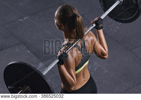 Female Bodybuilder Doing Back Squats In Gym. Beautiful Young Brunette Getting Ready To Do Barbell Sq