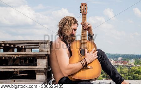 Guy Sitting Outdoor. Mature Hipster Musician With Beard. Brutal Caucasian Guy Playing Guitar. Countr