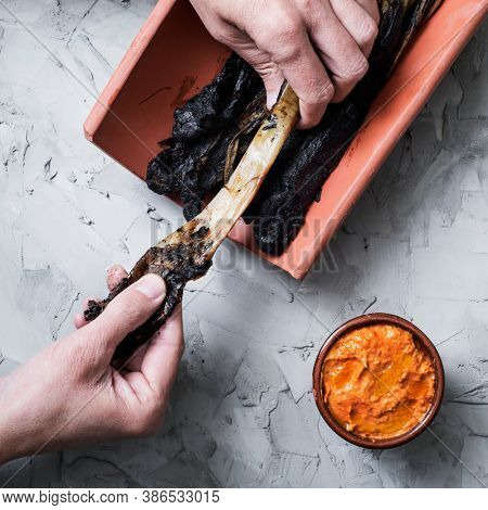 high angle view of a man peeling a grilled calcot, a sweet onion typical of Catalonia, Spain, next to an earthenware bowl with romesco sauce to dip in it, on a grary rustic surface