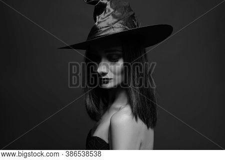 Mysterious Witch Wearing Hat On Dark Background. Black And White Effect