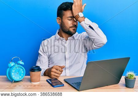 Handsome hispanic man working using laptop at the office surprised with hand on head for mistake, remember error. forgot, bad memory concept.
