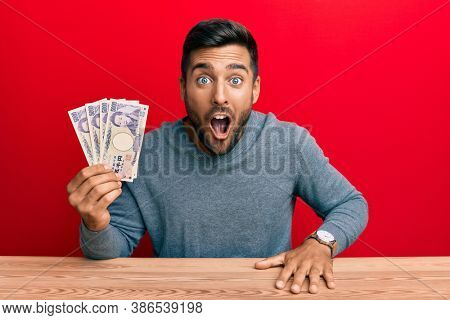 Handsome hispanic man holding japanese yen banknotes scared and amazed with open mouth for surprise, disbelief face