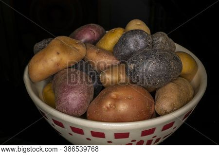 Otganic Purple And Brown Potatoes In Bowl With Black Background