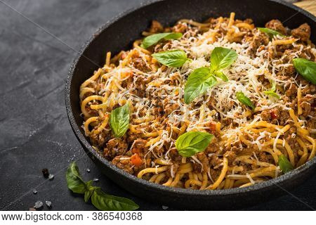 Pasta Bolognese, Meat Ragout In Tomato Sauce In The Skillet At Black Table. Italian Cuisine.