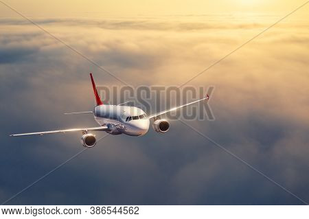 Airplane Is Flying Above The Clouds At Sunset In Summer. Landscape With Passenger Airplane, Low Clou