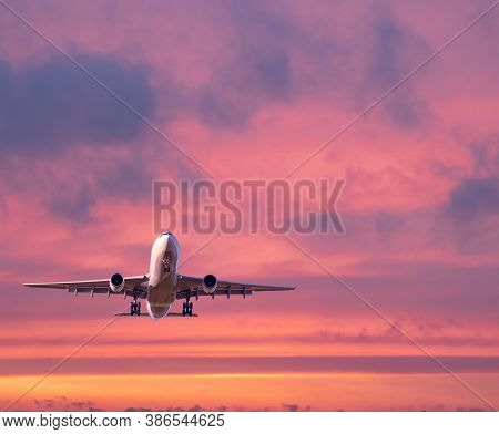 Airplane Is Flying In Colorful Sky At Sunset. Landscape With White Passenger Airplane, Purple Sky Wi