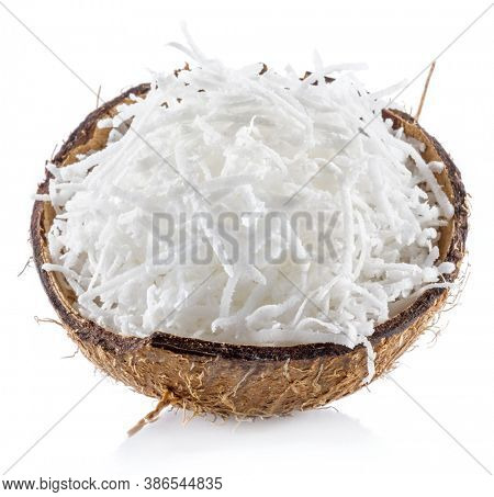 Shredded coconut flakes in the piece of coconut shell isolated on white background.