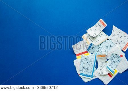 Torn Lottery Tickets With Numbers On A Dark Blue Background.  On The Pieces - Fragments Of The Words