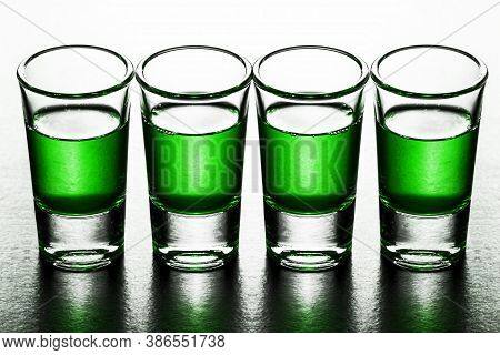 Four Vodka Shots Isolated On White. Vodka Glass In A Row. Green Booze Liquor. Weekend Party Backgrou