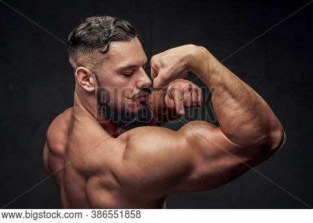 Brutal Bodybuilder With Black Beard And Mustache Points To His Huge Biceps In Gray Background.