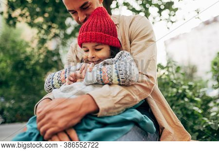 Bottom View Image Of Cute Little Girl In Red Cap Is Sitting In The Arms Of Her Dad. Father Embracing