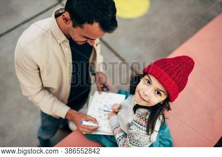 Top View Image Of Pretty Little Girl In Red Cap Drawing With Her Dad Outdoor After School. Father En