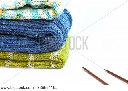 Stack Of Blue, Brown, Green Knitted Sweaters And Knitting Needles On A White Background. Home Comfor