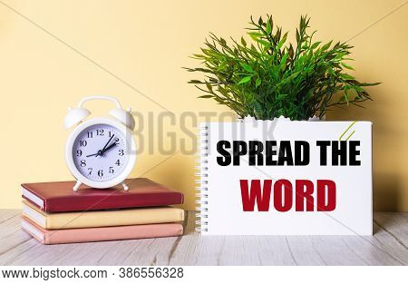 Spread The Word Is Written On A White Piece Of Paper Near A Green Plant, Diaries And A White Alarm C
